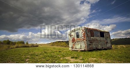 Abandoned, ruined trailer forgotten in the field