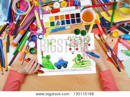 police car on outdoor, child drawing, top view hands with pencil painting picture on paper, artwork workplace