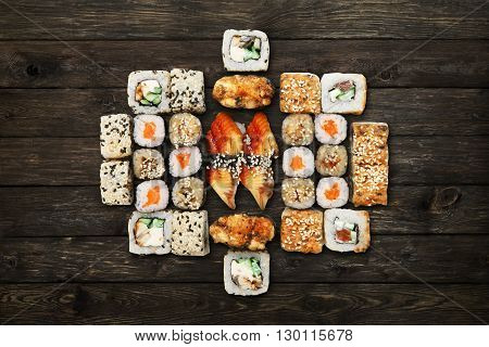 Japanese food restaurant, sushi maki gunkan roll plate or platter set. Unagi Sushi at rustic wood background. Top view, flat lay. Big party sushi set.