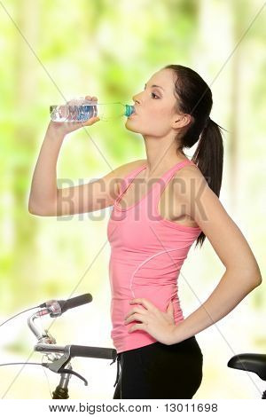 Attractive brunette woman with bike in forest drinking water
