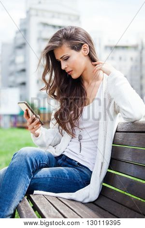 young woman sit on wooden bench in city park with smartphone in hand