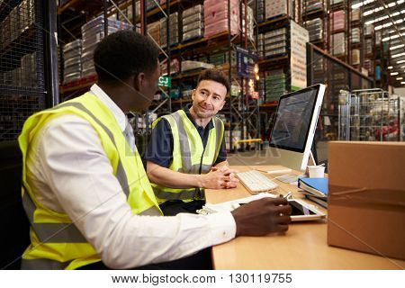 Staff discuss warehouse logistics in an on-site office