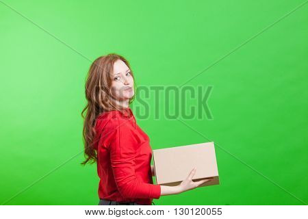 Woman holding cardboard box on green background
