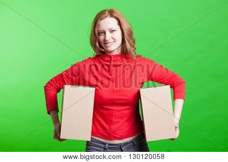 Woman holding cardboard boxes on green background