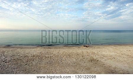 Sunrise time on the deserted beach with calm