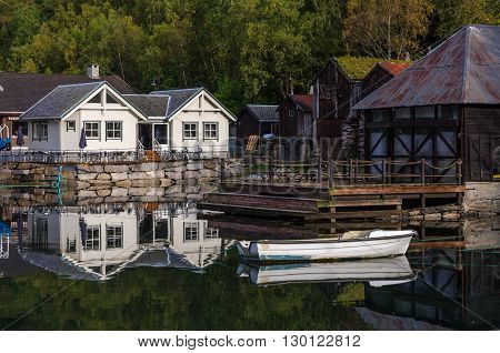 Reflections of sunlit Geranger harbor Norway at fall time