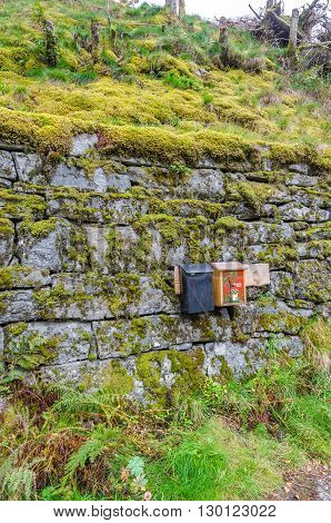 Two old mail boxes on stone wall with moss