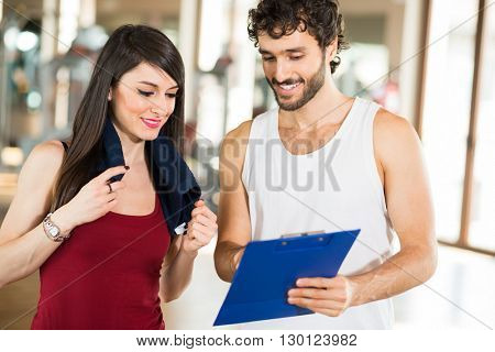 Woman talking to her personal trainer in a gym