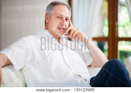 Portrait of an happy mature man relaxing on the couch