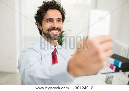 Portrait of a smiling businessman taking a selfie pic of himself