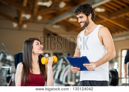 Woman working out in a gym while her personal trainer looks at the execution