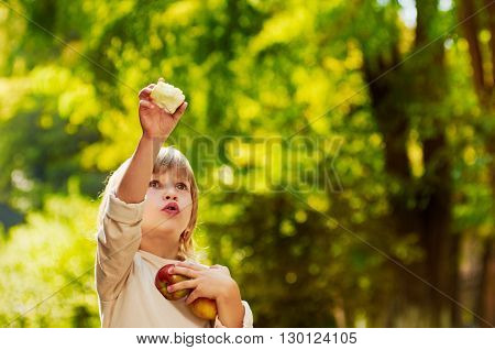 portrait of little handsome boy clasps apples by hands, he shows his hand up,  outdoor summer autumn warm