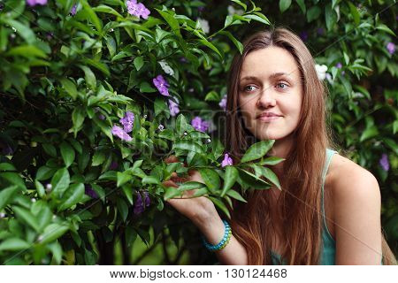 Beautiful girl with long brown hair on the background of the Bush. The girl smiles and looks thoughtfully to the side. Bush with little flowers on it.