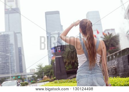 The girl looks at the skyscrapers. A girl stands amid the urban landscape. She turned her back and dressed in a jumpsuit.