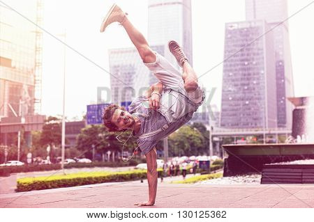 Young handsome guy is standing on the hand on the background of the urban landscape. Stylish dancer on city background.
