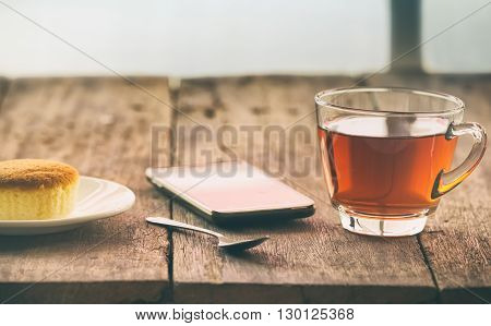 hot tea cup with butter cake and smartpho on the table on the winter day vintage toning