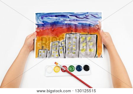 city skyline at sunset, skyscraper with light in window, home silhouette on dark sky background, child drawing, top view hands with pencil painting picture on paper, artwork workplace
