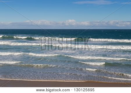 Morning view of the beach with breaking waves crashing sand on seashore, blurred background of blue sky in Victoria, Australia