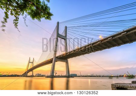 Ho Chi Minh city, Vietnam - January 14th, 2016: Moment dusk bridge with steel wire transfer time overnight, beautiful yellow sky, lights turned on honoring beauty bridge wire Ho Chi Minh city, Vietnam