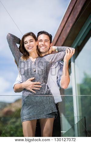 Low angle view of romantic young couple embracing in balcony at resort
