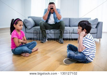 Annoyed father sitting on sofa while kids fighting and teasing each other at home