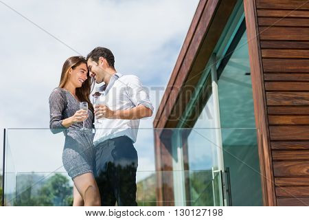 Low angle view of happy couple with champagne at balcony in resort