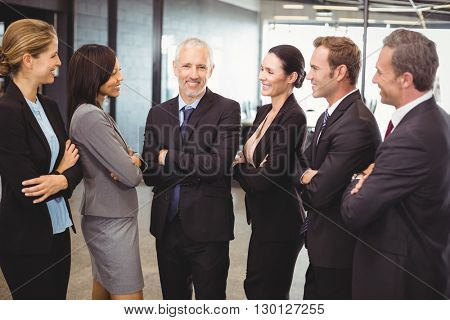 Businesspeople standing together with arms crossed in office