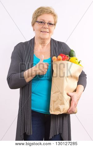 Happy elderly senior woman holding shopping bag with fruits and vegetables and showing thumbs up healthy nutrition in old age