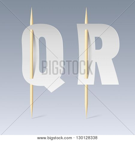 White paper cut font on toothpicks on grey background. Q and R letters