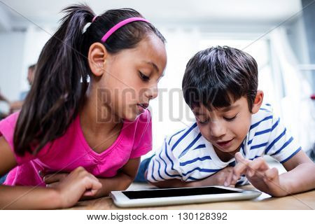 Brother and sister lying on floor and using digital tablet in living room