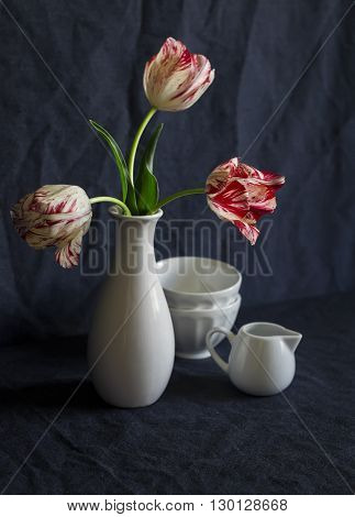 Bouquet of tulips and vintage crockery on a dark blue background. Still life in vintage style