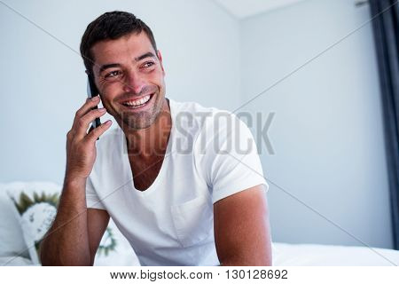Happy man talking on phone in bedroom