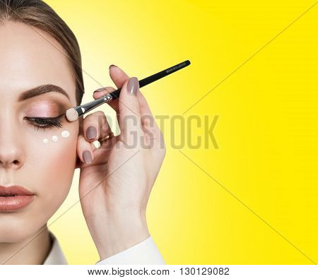 Beautiful woman face with make-up and cream dotts on a cheek on the yellow background. Skin care concept.