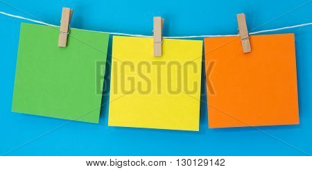 Three brightly colored note squares hanging on a white string line in front of a bright blue background.