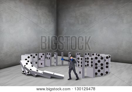 Businessman boxing domino in rough gray room