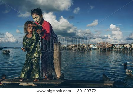 Denawan Island Sabah Malaysia - April 30 2016 : A mother helping her child to stand on a broken wooden bridge. Both were wearing a traditional clothing with the mother had a natural paste on her face as the natural sun block.