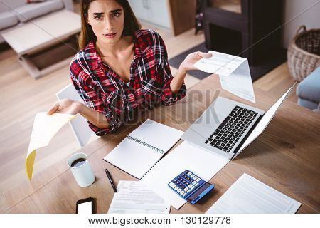 Portrait of tensed woman showing documents while sitting at table
