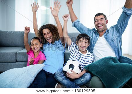 Family watching match on television at home