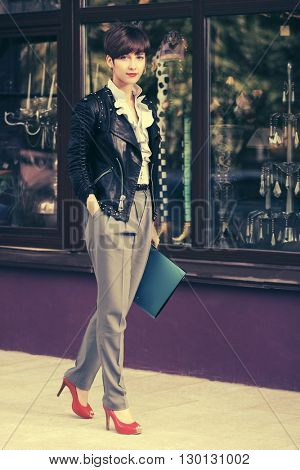 Young fashion business woman with a folders on city street