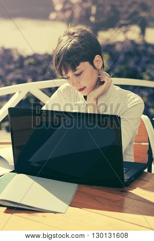 Happy young business woman with laptop at sidewalk cafe
