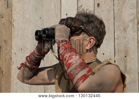 Steampunk man wearing glasses looks through a binoculars. Post-apocalypse fantasy