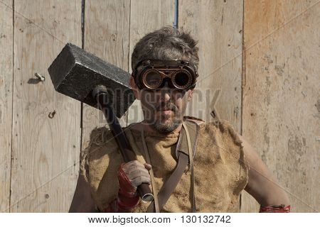 Steampunk man wearing glasses with sledge hammer