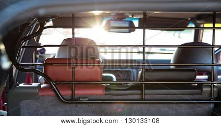 The car's interior in the sun. Back view. The dashboard is blurred.