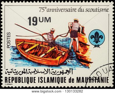 MOSCOW RUSSIA - MAY 14 2016: A stamp printed in Mauritania shows two boyscout moor a boat series