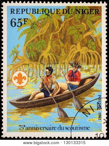 MOSCOW RUSSIA - MAY 14 2016: A stamp printed in Niger shows two boyscout in canoe on the river among mangroves series
