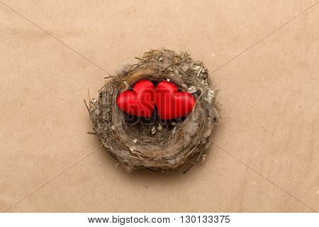 Souvenir red hearts in the real bird's nest from a grass and down