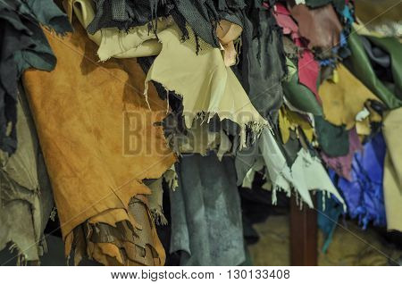 Close-up of various colors of leather textiles. Leather hanging at a leather factory for production. The leather sheets are in sharp focus and no human figure or body part are in the image.