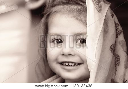 Portrait of a smiling little girl with headscarf in black white tones