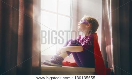 Little child girl plays superhero. Child sitting on the window. Girl power concept.