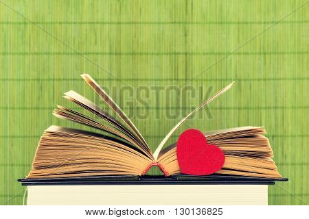 The opened book with the turned yellow pages and heart on a green background from bamboo sticks